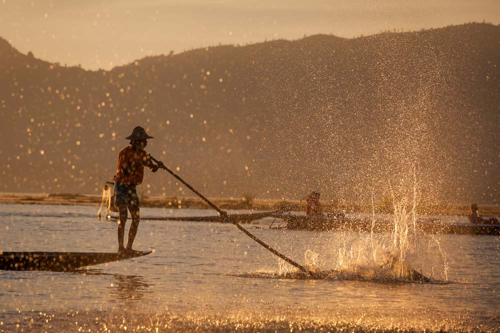 A fisher splashes into the water to scare the fish into his net at Inle Lake. Photo: John Einar Sandvand