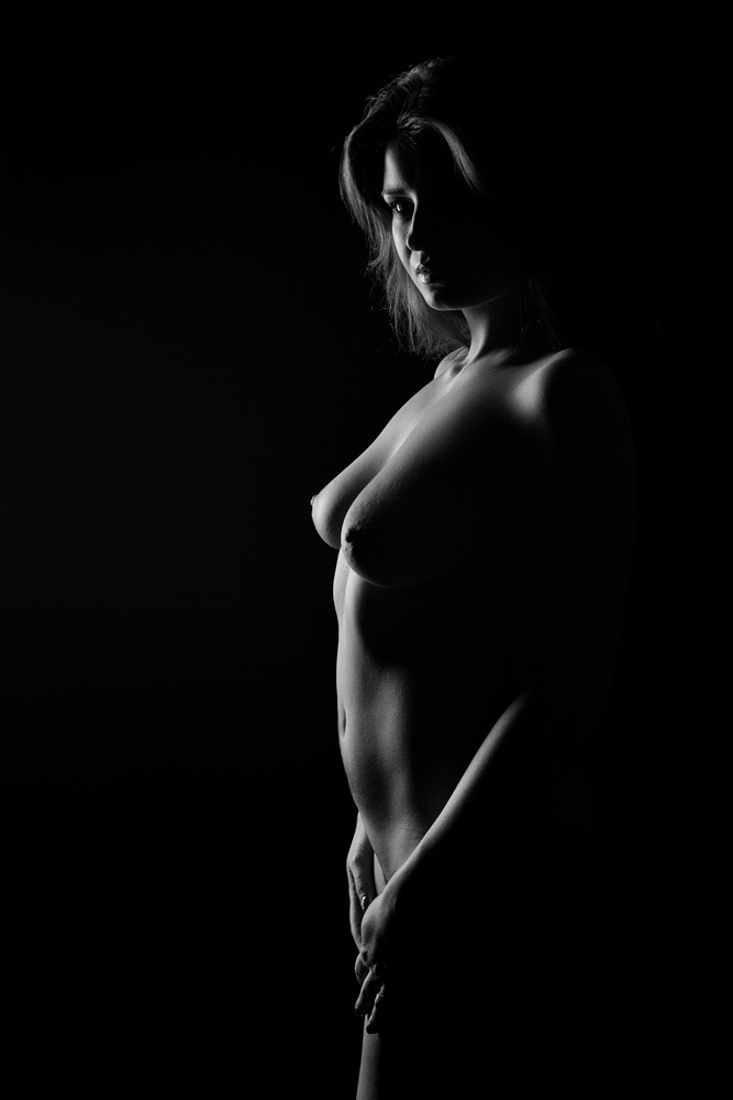 Low key photo taken with only one light - a softbox with grid  from slightly behind the model on one side. Photo: John Einar Sandvand